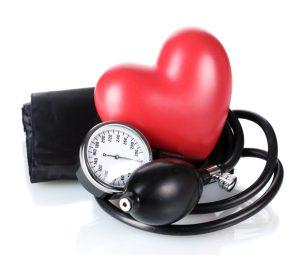Ein rotes Herz mit Blutdruckmessgerät vor weißem Hintergrund