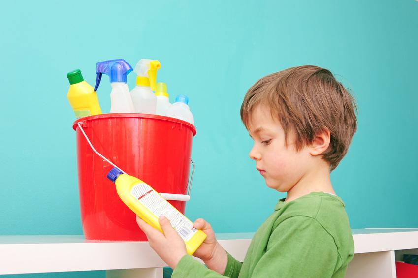 Kind mit Eimer betrachtet Putzmittel