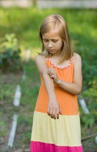 Ein Mädchen im Sommerkleid kratzt sich am Arm
