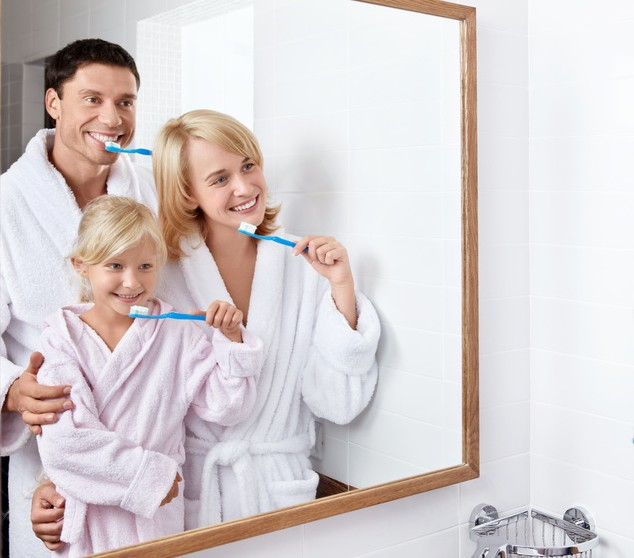 Vater, Mutte rund Kind putzen sich im Badezimmer die Zähne