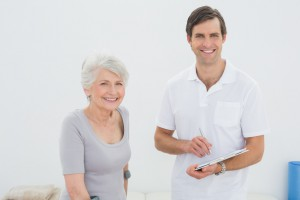 Ältere Frau mit jungem Physiotherapeutenp