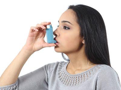 Eine Frau behandelt Asthma mit einem Inhalator