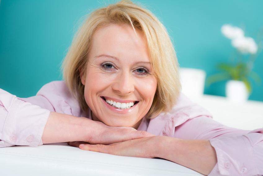 Eine blonde Frau 40+ schaut lächelnd in die Kamera