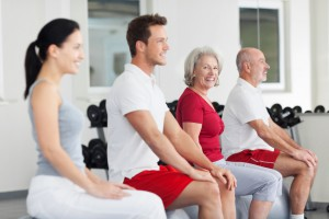 Zwei Frauen und zwei Männer sitzen auf Gymnastikbällen