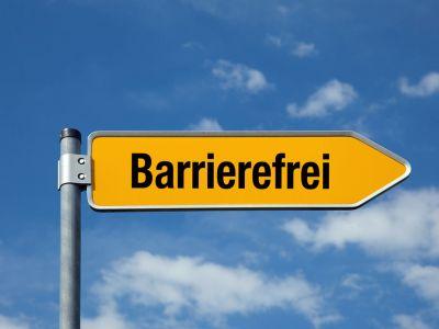 gelber Pfeil Schrift Barrierefrei vor blauem Himmel