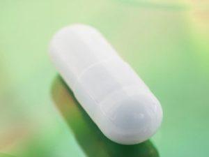 Weiße Pille auf grünem Grund