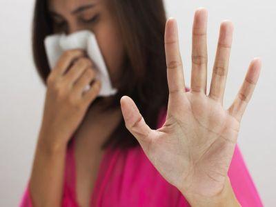 Frau schnupft wehrt mit Hand ab