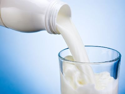 Aus weißer Milchflasche fließt Milch in ein Glas vor hellblauem Hintergrund