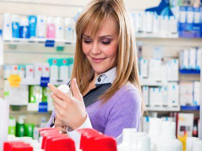 Portrait einer blonden Frau die sich Produkte in der Apotheke ansieht.