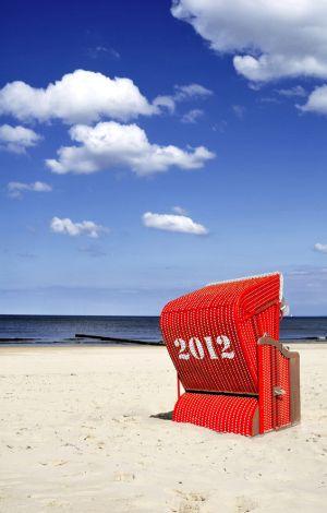 Roter Strandkorb vor leicht bewölktem, blauem Himmel.