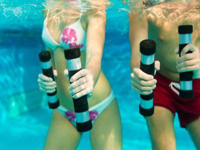 Zwei sprtliche Menschen in Badekleidung betreiben Unterwassergymnastik mit Hanteln.