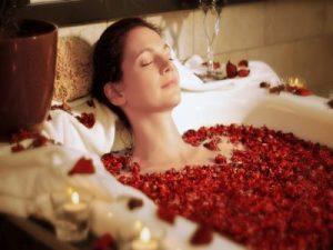 Eine Frau liegt in einer Badewanne mit Kerzenlicht und Rosenblättern