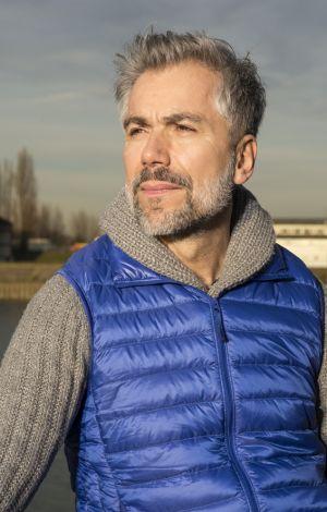 Grauhariger Mann mit blauer Weste in der Abendsonne