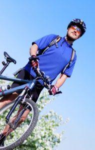 Sportlicher Mann mit Helm steht neben seinem Farrad.