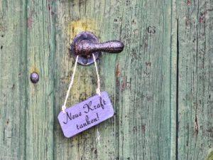 """Ein helllilafarbenens Schild mit den Worten """"Neue Kraft tanken""""hängt an der Türklinke einer antiken Tür.."""