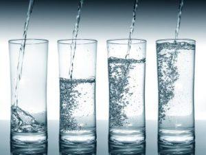4 unterschiedlich hoch gefüllte Wassergläser.