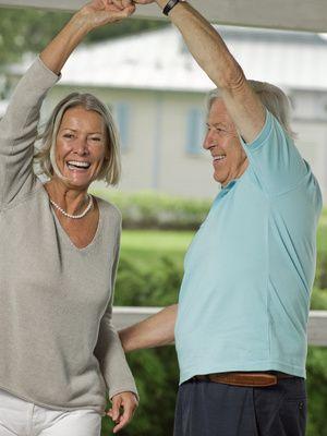 Ein fröhliches, älters Paar tanzt beschwingt.