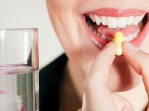 Frau schluckt Tablette, ein Glas Wasser daneben.