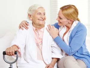 Eine junge Frau hält eine Seniorin im Arm.