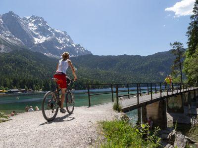 Jüngere Frau auf Bike vor dem überqueren einer Brücke über einen See vor Bergkulisse