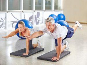 Mann und Frau machen gemeinsam Gymnastik im Fitnesscenter