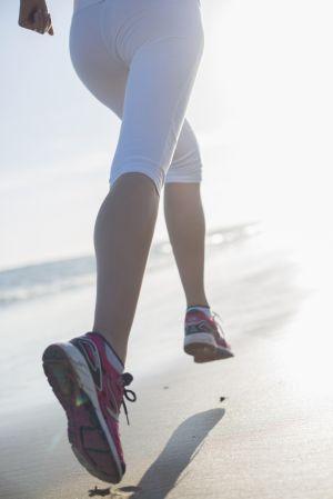 Die Beine einer sportlichen Frau, die am Strand joggt.