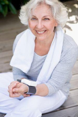 attraktive, grauhaarige Frau misst den Blutdruck