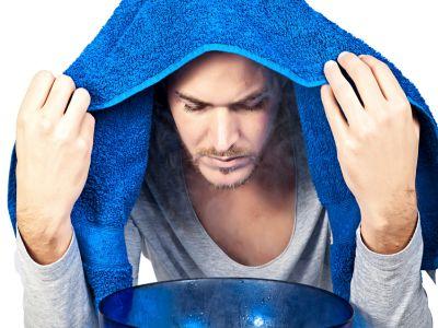 Mann hat ein blaues Handtuch über dem Kopf und beugt sich über eine Schüssel mit dampfendem Wasser.