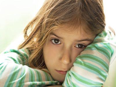 Trauriges Kind mit gegestreiftem Shirt hat den Kopf auf den Arm gelegt.