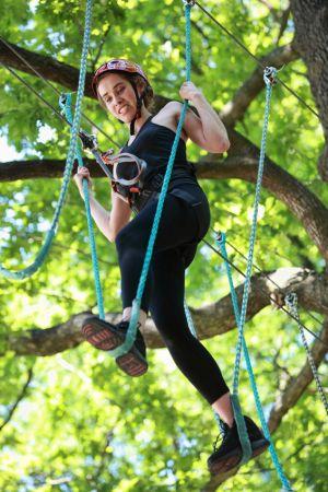 Eine Frau mit ängstlichem Gesicht im Baum eines Kletterparks.