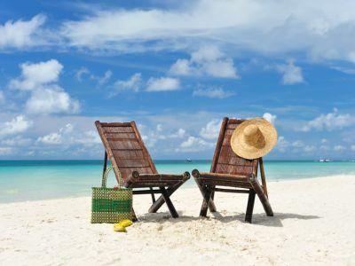Weißer Sand, türkisfarbenes Wasser, hellblauer Wolkenhimmel, zwei Strandstühle mit Hut und Tasche