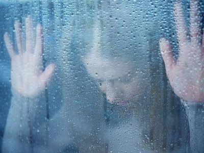 Eine junge Frau lehnt mit gesenktem Kopf die Hände an eine regennasse Glasscheibe