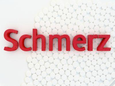 Auf weissen Tabletten steht in roten 3D-Buschstaben das Wort Schmerz.