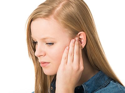 Eine junge Frau hält sich ihr Ohr.