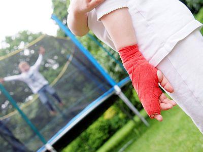Ein Mädchen mit Gipsverband an der Hand schaut einem Kind auf dem Trampolin zu.