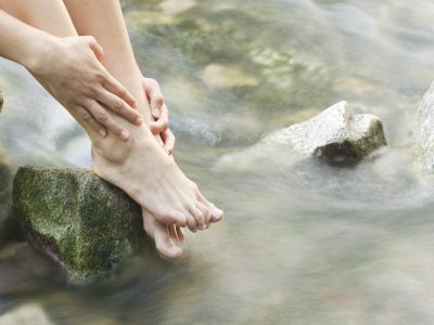 Eine Frau taucht ihre Füße in einen Waldbachlauf.