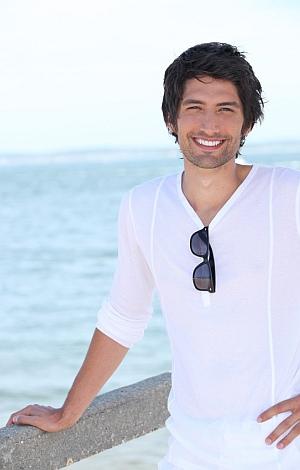 Junger Mann am Meer lächelt mit sehr weissen Zähnen
