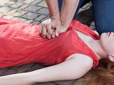 Ein Mann führt an einer Frau, die auf dem Boden liegt, eine Herzmassage durch.