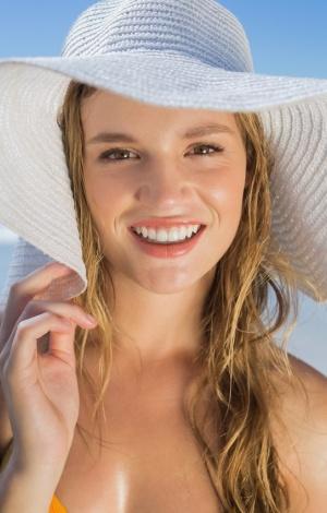 Eine junge blonde Frau schützt sich mit einem weissen Hut.