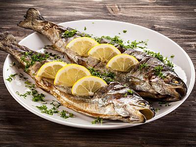 Gegrillter Fisch mit Zitronen und Kräutern belegt.
