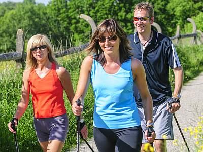 Drei fröhlich lächelnde Menschen betreiben Nordic Walking am Feldrand.