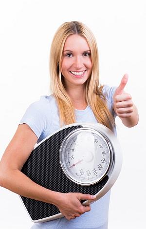Eien lächelnde, blonde Frau hat eine Waage unter dem Arm und hält einen Daumen in die Höhe.