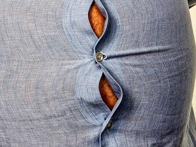 Mann mit dickem Bauch sprengt sein hellblaues Hemd.