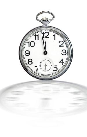 Eine Taschenuhr zeigt kurz vor 12 Uhr.