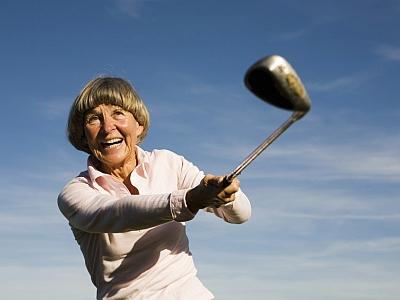 Ältere , fröhliche Frau mit Golfschläger
