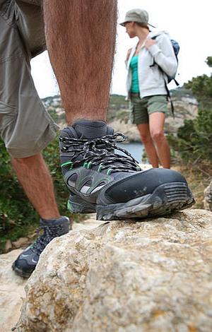 Ein Wanderer stützt einen Fuß auf den Stein, im Hintergrund eine Wanderin.