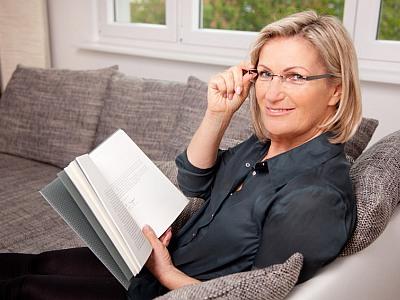 Frau sitzt mit einem Buch auf dem Sofa und lächelt in die Kamera.