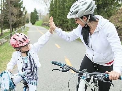 Mutter und Tochter fahren gemeinsam Rad und klatschen sich ab.