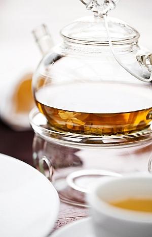Eine gläserne Kanne mit Tee auf einem Stövchen und eine Teetasse.