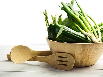 Eine Holtschüssel mit grünem Gemüse und Holzsalatbesteck.
